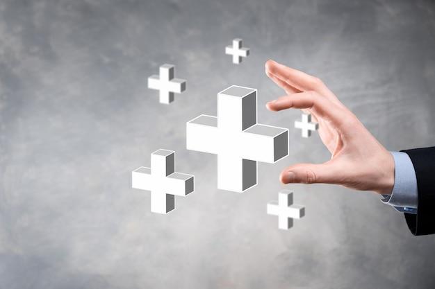 ビジネスマンは3dプラスアイコンを持ち、男性は手に持って利益、利益、開発、プラス記号で表されるcsrなどのポジティブなものを提供します。手にはプラス記号が表示されます。