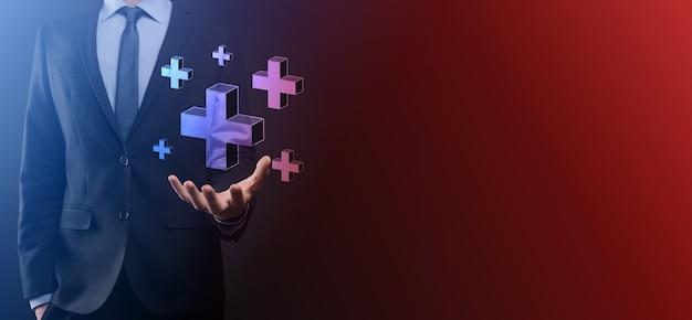 사업가는 3d 플러스 아이콘을 잡고, 남자는 손에 잡고 이익, 혜택, 개발, csr과 같은 긍정적 인 것을 더하기 기호로 표시합니다.