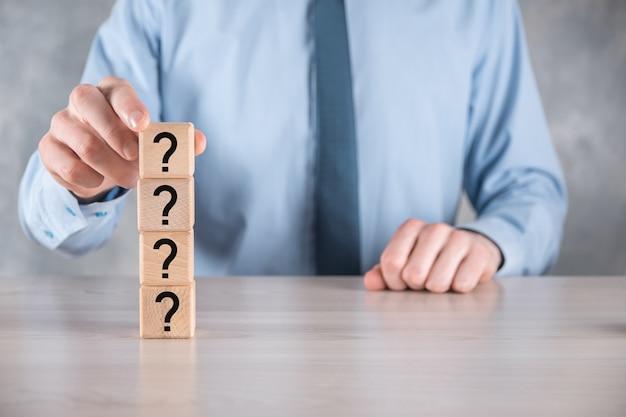 Бизнесмен удерживайте и поместите деревянную форму блока куба с вопросительными знаками на серый стол. место для текста. концепция для путаницы, вопроса или решения.