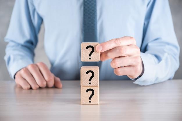 ビジネスマンは、灰色のテーブルに疑問符の付いた木製の立方体のブロックの形を保持し、置きます。混乱、質問または解決のためのtext.conceptのためのスペース。