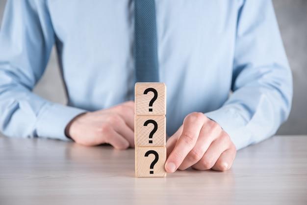 사업가 누르고 회색 테이블에 물음표와 함께 나무 큐브 블록 모양을 넣어. 텍스트를위한 공간. 혼란, 질문 또는 해결책을위한 개념.