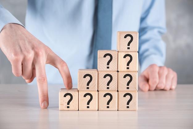 ビジネスマンは、灰色のテーブルに疑問符の付いた木製の立方体ブロックの形を保持して置きます。混乱、質問、または解決のための text.concept のためのスペース。