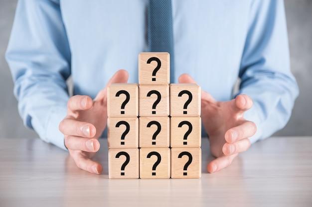 사업가 누르고 회색 테이블에 물음표와 함께 나무 큐브 블록 모양을 넣어. 텍스트를위한 공간. 혼란, 질문 또는 솔루션을위한 개념입니다.