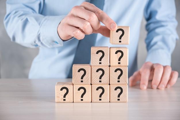 ビジネスマンは、灰色のテーブルに疑問符の付いた木製の立方体のブロックの形を持って置きます