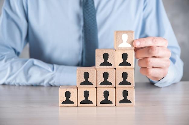 ビジネスマンは、灰色のテーブルにユーザーアイコンと木製の立方体のブロックの形を保持して置きます。テキスト用のスペース。インターネットアイコンはフォアグラウンドにインターフェイスします。グローバルネットワークメディアの概念、仮想画面上の連絡先、コピースペース。