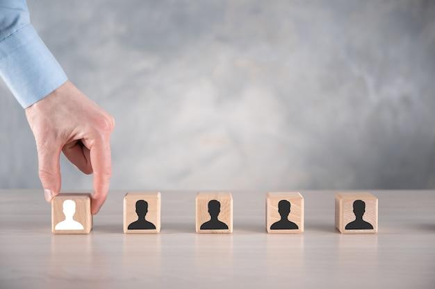 ビジネスマンは、灰色のテーブルにユーザーアイコンと木製の立方体のブロックの形を保持して置きます。テキスト用のスペース。インターネットアイコンはフォアグラウンドにインターフェイスします。グローバルネットワークメディアの概念、仮想画面上の連絡先、コピースペース