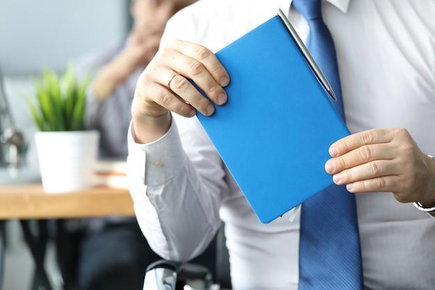 Бизнесмен держать синий дневник в руке.