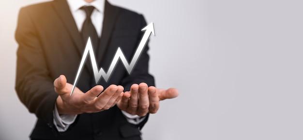 사업가는 화면 성장 그래프, 긍정적인 성장 아이콘의 화살표에 그림을 들고 있습니다. 위쪽 화살표가 있는 창의적인 비즈니스 차트를 가리키고 있습니다. 금융, 비즈니스 성장 개념입니다.