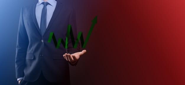 ビジネスマンは、画面の成長グラフ、正の成長アイコンの矢印に描画を保持します。上向きの矢印で創造的なビジネスチャートを指しています。財務、ビジネスの成長の概念。