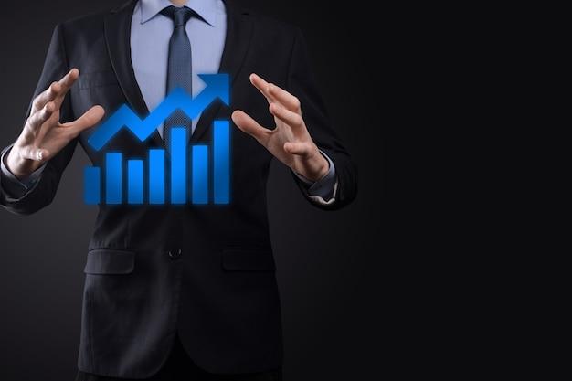 Бизнесмен удерживает рисунок на экране растущего графика, стрелка значка положительного роста. указывая на творческую бизнес-диаграмму с восходящими стрелками.