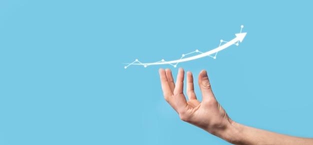 Бизнесмен удерживает рисунок на растущем графике экрана, стрелка значка положительного роста. указывая на творческий бизнес-диаграмму с восходящими стрелками.