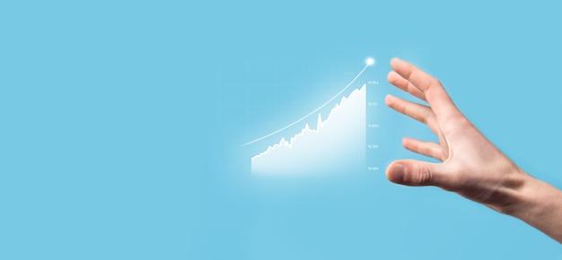 Бизнесмен удерживает рисунок на экране растущего графика, стрелка значка положительного роста. указывая на творческую бизнес-диаграмму с восходящими стрелками. концепция финансового, бизнес-роста.