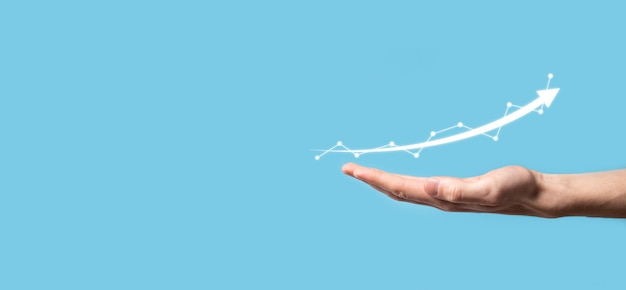 ビジネスマンは、画面の成長グラフ、正の成長アイコンの矢印で描画を保持します。上向きの矢印で創造的なビジネスチャートを指しています。財務、ビジネスの成長の概念