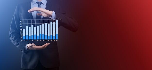 Бизнесмен удерживает рисунок на растущем графике экрана, стрелка значка положительного роста. указывая на диаграмму творческого бизнеса