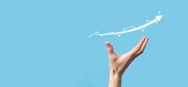 ビジネスマンは、画面の成長グラフ、正の成長アイコンの矢印で描画を保持します。創造的なビジネスチャートを指しています。