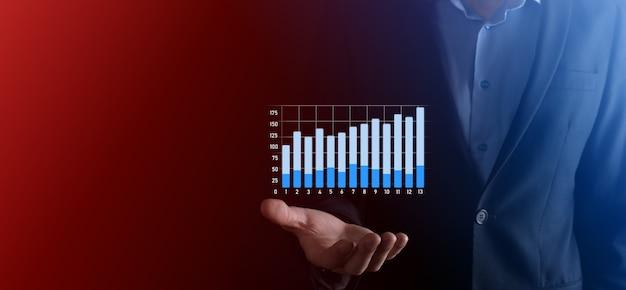 Бизнесмен удерживайте рисунок на растущем графике экрана, стрелка значка положительного роста