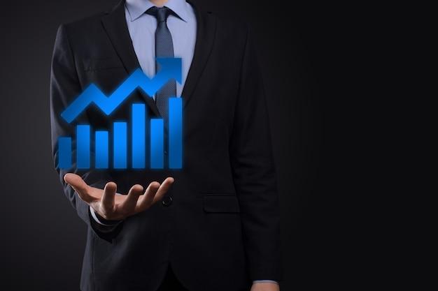 ビジネスマンは、画面の成長グラフ、正の成長アイコンの矢印に描画を保持します。 Premium写真