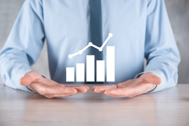 ビジネスマンは、画面の成長グラフ、正の成長アイコンの矢印に描画を保持します