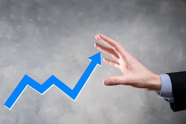 ビジネスマンは、画面の成長グラフ、正の成長のシンボルの矢印、上向きの矢印で創造的なビジネスチャートを指しています。