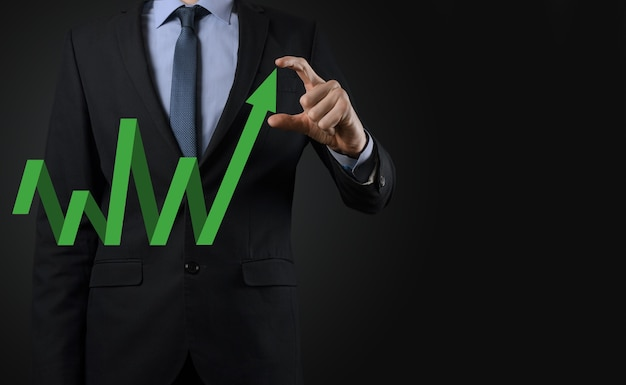 Businessman hold drawing on screen growing graph, arrow of positive growth icon.pointing at creative business chart with upward arrows.