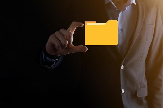 ビジネスマンはフォルダアイコンを保持します。最新のコンピュータを使用してitコンサルタントによってセットアップされたドキュメント管理システムまたはdmsは、管理情報と企業ファイルを検索しています。ビジネス処理、