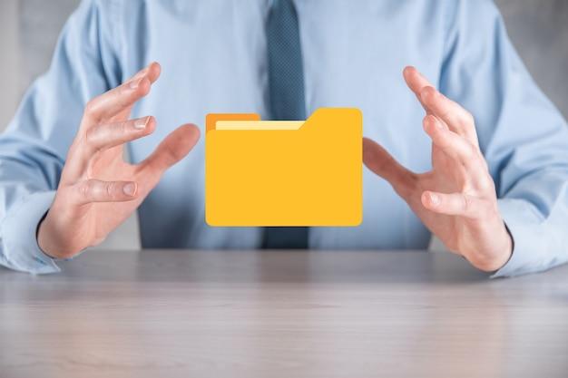 ビジネスマンは、フォルダー アイコンを保持します。最新のコンピューターを使用した it コンサルタントによるドキュメント管理システムまたは dms セットアップは、管理情報と企業ファイルを検索しています。