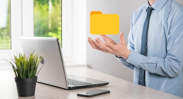 Значок папки удержания бизнесмена. система управления документами или установка dms ит-консультантом с современным компьютером ищут управляющую информацию и корпоративные файлы. Premium Фотографии