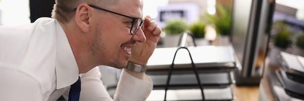 ビジネスマンは彼の手で眼鏡を保持し、職場でコンピューターのモニターを調べます。幸せな男は、図とドキュメントを保持し、オフィスで彼の手にサインインします。