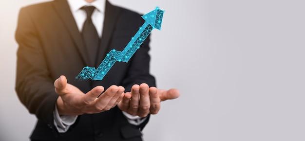 사업가는 그래프, 긍정적인 성장 아이콘의 화살표를 위쪽 화살표가 있는 창의적인 비즈니스 차트를 가리키고 있습니다. 금융, 비즈니스 성장 개념입니다. 낮은 다각형. 매출 증가 또는 가치 증가