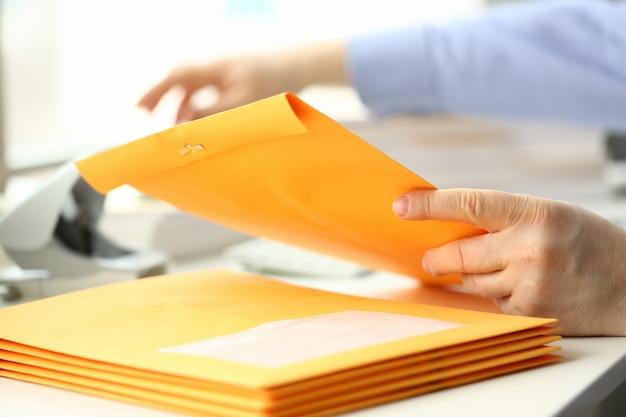 ビジネスマン保持手黄色メール封筒
