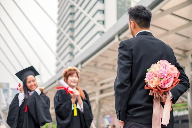 사업가는 젊은 여성의 학사 학위 졸업을 축하하기 위해 꽃다발을 숨기고 있다