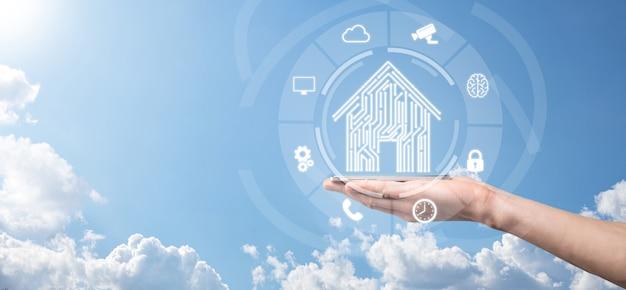 사업가는 집 아이콘을 잡고 있습니다. 스마트 홈 제어, 지능형 집 및 홈 자동화 앱 개념입니다. pcb 디자인 및 스마트 폰을 사용하는 사람입니다. 혁신 기술 인터넷 네트워크 개념입니다.