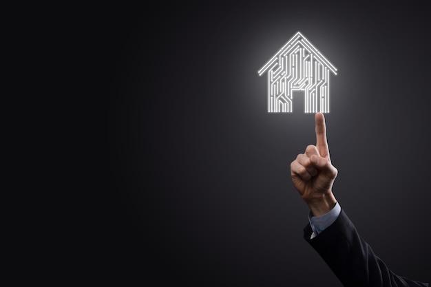 ビジネスマンは家のアイコンを保持します。スマートホーム制御、インテリジェントハウス、およびホームオートメーションアプリのコンセプト。pcbデザインとスマートフォンを持つ人。イノベーション技術インターネットネットワークコンセプト。