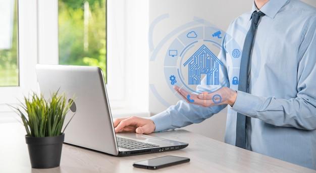 ビジネスマンは家のアイコンを保持します。スマートホーム制御、インテリジェントハウス、およびホームオートメーションアプリのコンセプト。pcbデザインとスマートフォンを持つ人。イノベーションテクノロジーインターネットネットワークコンセプト。