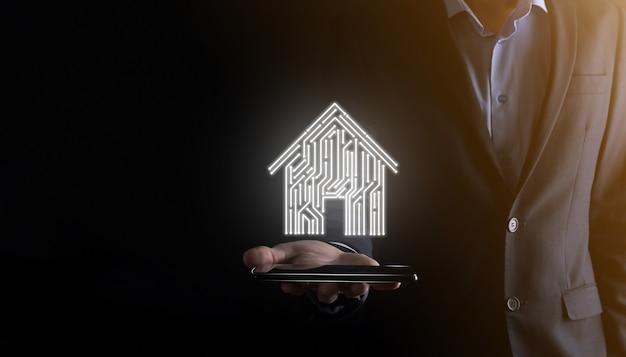사업가 홀드 하우스 아이콘 스마트 홈 제어, 지능형 하우스 및 홈 오토메이션 앱 개념. pcb 디자인과 스마트 폰을 가진 사람. 혁신 기술 인터넷 네트워크 개념.