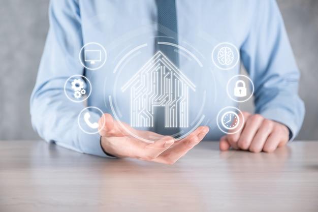 ビジネスマンは家のアイコンを保持します。スマートホーム制御、インテリジェントハウス、ホームオートメーションアプリのコンセプト。pcbデザインとスマートフォンを持つ人。イノベーション テクノロジー インターネット ネットワーク コンセプト。