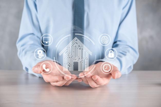 Бизнесмен держать значок дома. умный дом, управляемый, умный дом и концепция приложения домашней автоматизации. дизайн печатной платы и человек со смартфоном. концепция сети интернет инновационных технологий.
