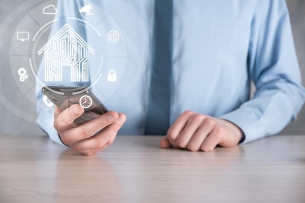 사업가는 집 아이콘을 잡고 있습니다. 스마트 홈 제어, 지능형 집 및 홈 자동화 앱 개념입니다.