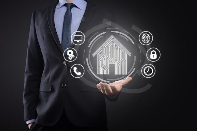 사업가는 집 아이콘을 잡고 있습니다. 스마트 홈 제어, 지능형 집 및 홈 자동화 앱 개념