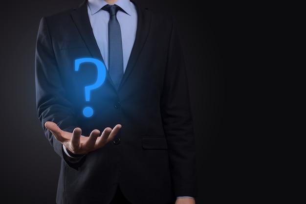 Бизнесмен держать интерфейс вопросительные знаки подписать сеть.