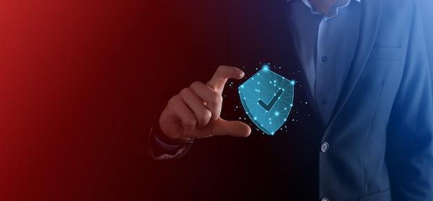 Бизнесмен держит низкополигональный щит со значком галочки. концепция системы безопасного доступа. финансовая гарантия для бизнеса для инвестиций. концепция антивируса. технологическая безопасность. сеть защиты, безопасные данные.
