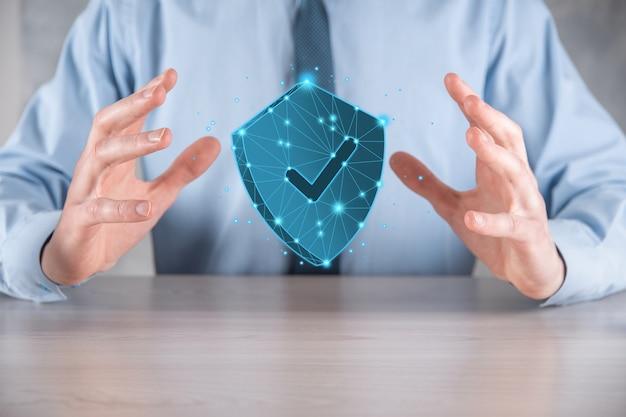 사업가는 눈금 아이콘이 있는 낮은 폴리 다각형 방패를 들고 있습니다. 보안 액세스 시스템 개념입니다. 투자에 대한 비즈니스 재정 보증입니다. 기술 보안입니다. 보호 네트워크, 안전한 데이터입니다.
