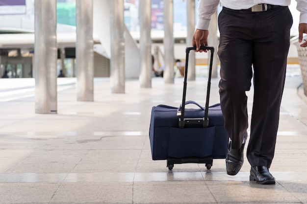 Businessman hold luggage travel passenger bag of tourist traveller on walk way in gate terminal.