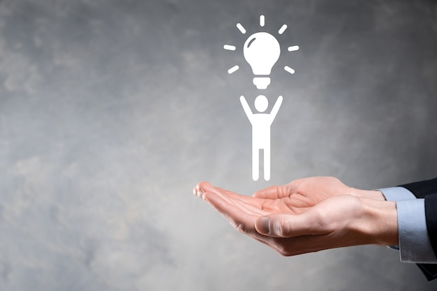 Businessman hold man icon with light bulbs, ideas of new ideas with innovative technology and creativity. concept creativity with bulbs that shine glitter.