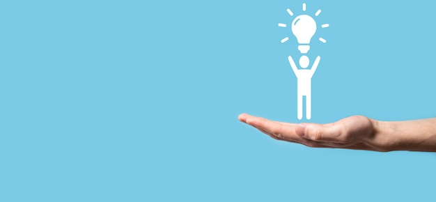 사업가는 전구, 혁신적인 기술 및 창의성을 갖춘 새로운 아이디어의 아이디어를 가진 남자 아이콘을 보유합니다. 반짝이는 전구로 개념 창의성.
