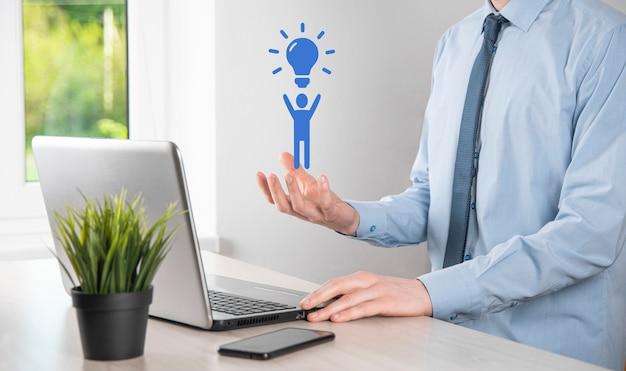 ビジネスマンは、電球、革新的な技術と創造性を備えた新しいアイデアのアイデアで男のアイコンを保持します。キラキラと輝く球根のコンセプトクリエイティビティ。