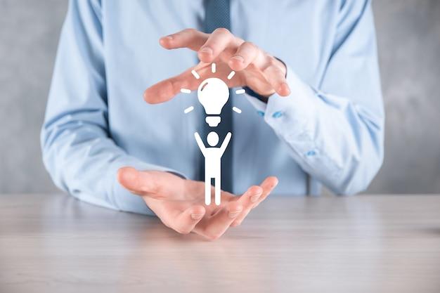 Бизнесмен удерживайте значок человека с лампочками, идеями новых идей с инновационными технологиями и творчеством. концепция творчества с луковицами, которые сияют блеском.