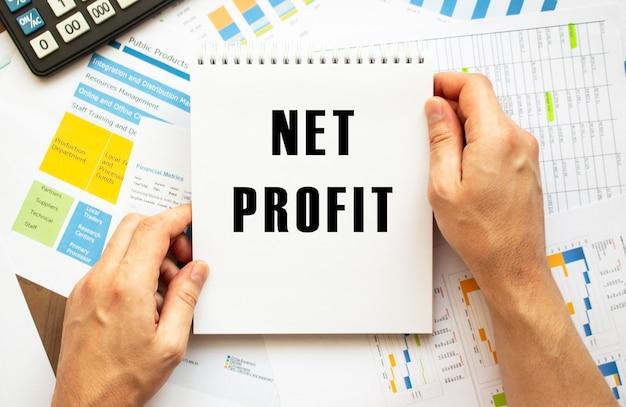 ビジネスマンは、テキストnetprofitでメモ帳を保持します