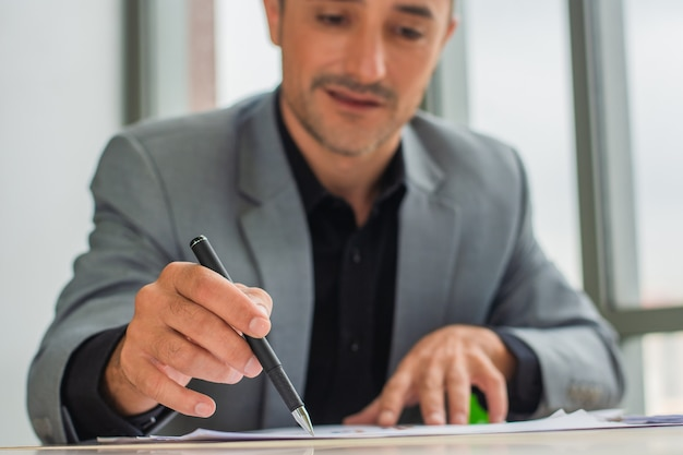Businessman hold pen signature on document