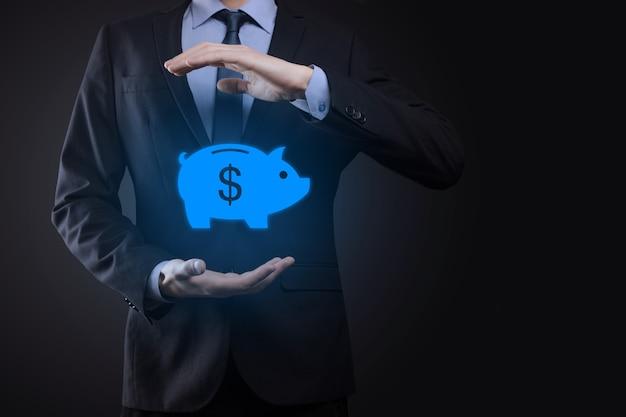 Бизнесмен держать значок копилку. бизнес и планирование расходов денег, и инвестиционный бюджет, бизнес сберегая деньги concept.save или инвестиции.